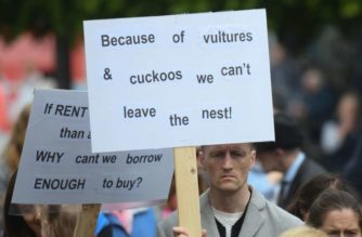 """man holds a sign which reads """"Because of vultures & cuckoos we can't leave the nest!"""""""